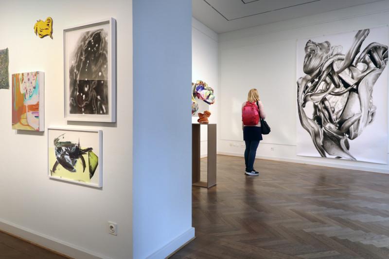 Links sind mehrere kleine Bilder an der Wand. Rechts: Blick in den zweiten Raum. Dort steht eine Besucherin vor der großformatigen Zeichnung von Peter Hock.