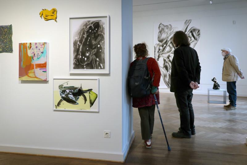 Ausstellungsansicht: fünf kleinformatige Bilder hängen links an der Wand, rechts Blick in den zweiten Ausstellungsraum mit Besuchenden der Ausstellung.