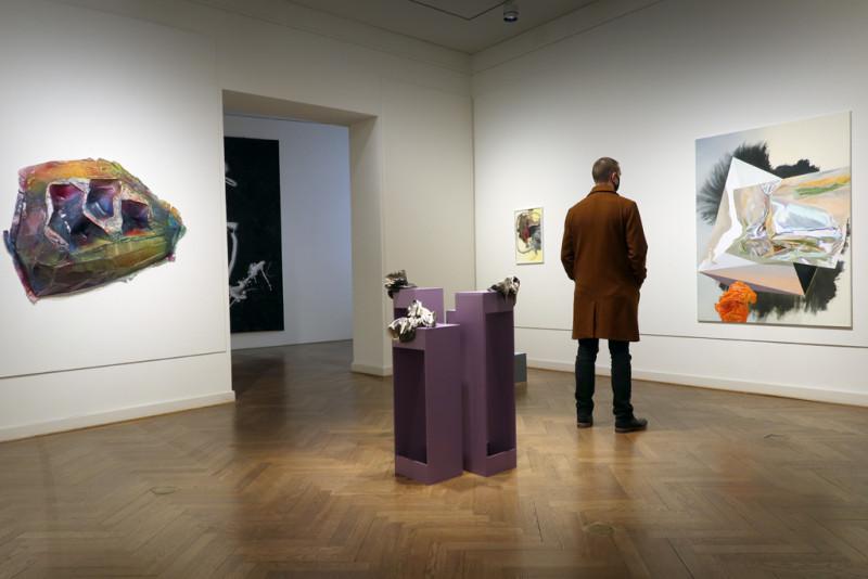 Besucher betrachtet ein Bild von der Künstlerin Maja Rohwetter, Außerdem im Raum sind kleine Keramik Skulpturen in der Mitte des Raums und ein buntes Kunstobjekt an der Wand.