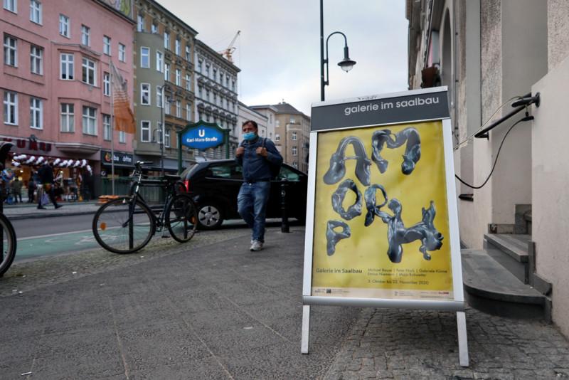 Das Schild mit dem Plakat zur Ausstellung mit dem Schriftzug AMORPH steht auf der Karl-Marx-Straße vor dem Eingang zur Galerie im Saalbau