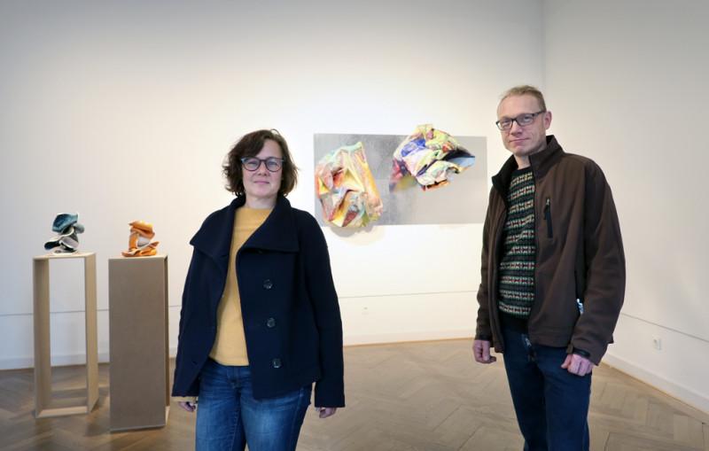 Gabriele Künne rechts von ihren Keramikarbeiten auf Sockel und Enrico Niemann rechts von seinen bunten Objekten an der Wand.