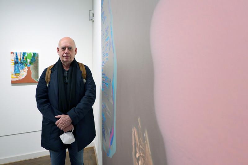 Michael Bause steht links von seinem Werk in der Ausstellung