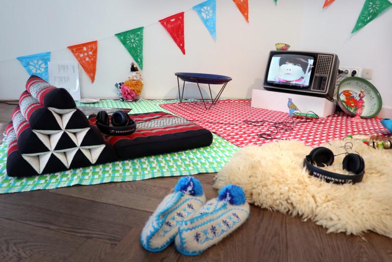 ein Schafsfell, Teppiche und Stoffschuhe liegen auf dem Boden