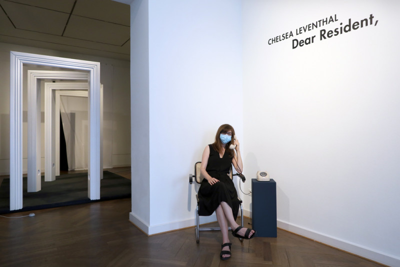 die Künstlerin lauscht den Geräuschen aus einem  beigen Drehscheibentelefon