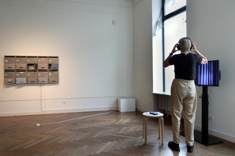 eine Besucherin hört und sieht sich das Werk