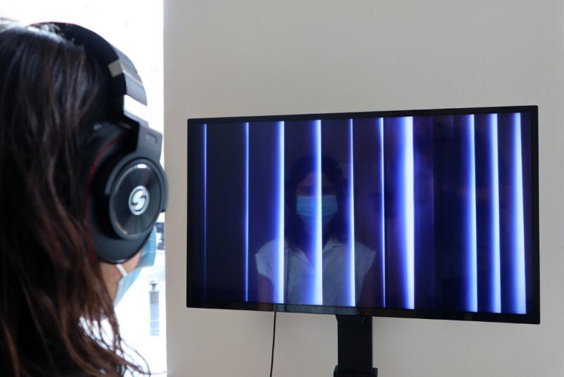 eine Besucherin mit Mundschutz und Kopfhörern sieht sich das Video der Künstlerin an