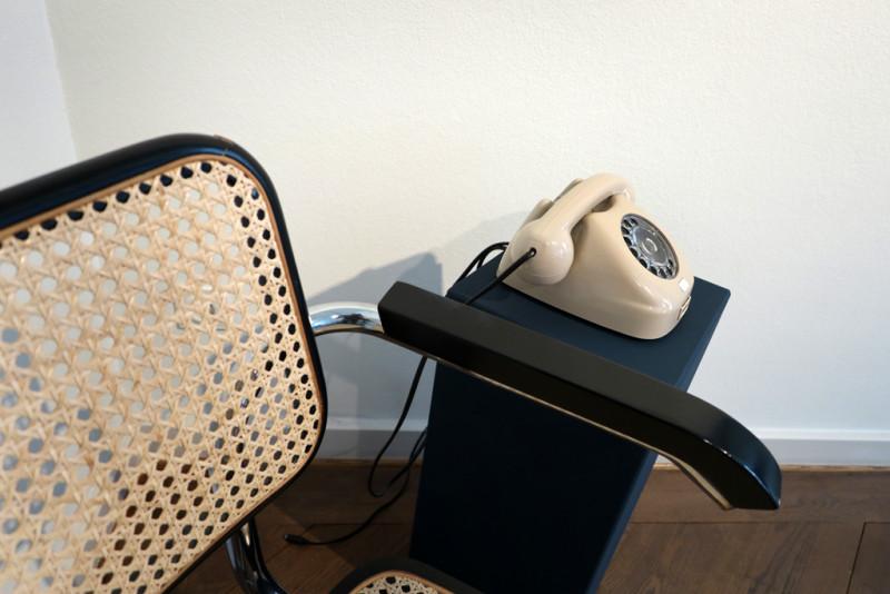 ein beiges Drehscheibentelefon steht auf einem blauen Sockel