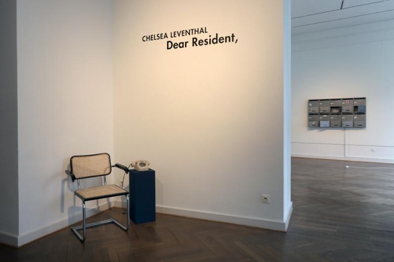 ein Stuhl steht in der Ecke und daneben ein Telefon auf einem blauen Sockel