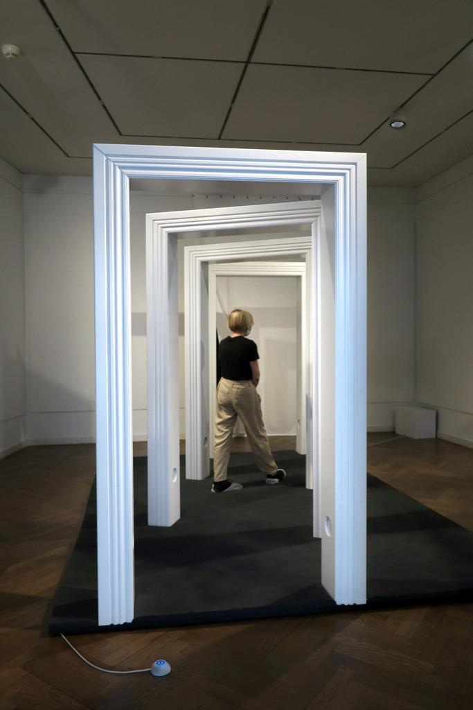 eine Besucherin durchschreitet die großen weißen Türrahmen
