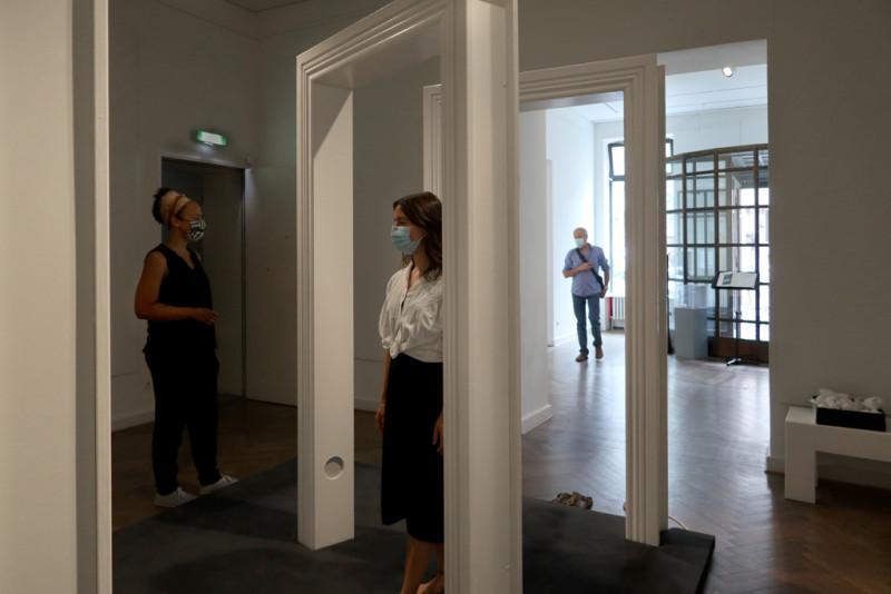 Besucher durchschreiten die großen weißen Türrahmen in der Ausstellung