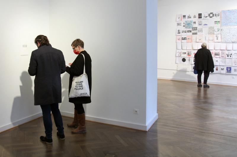 Ein Pärchen steht vor Eugen Gomringers Arbeit