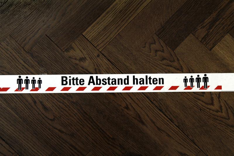 """Markierungsband auf dem Boden mit dem Hinweis """"Bitte Abstand halten"""