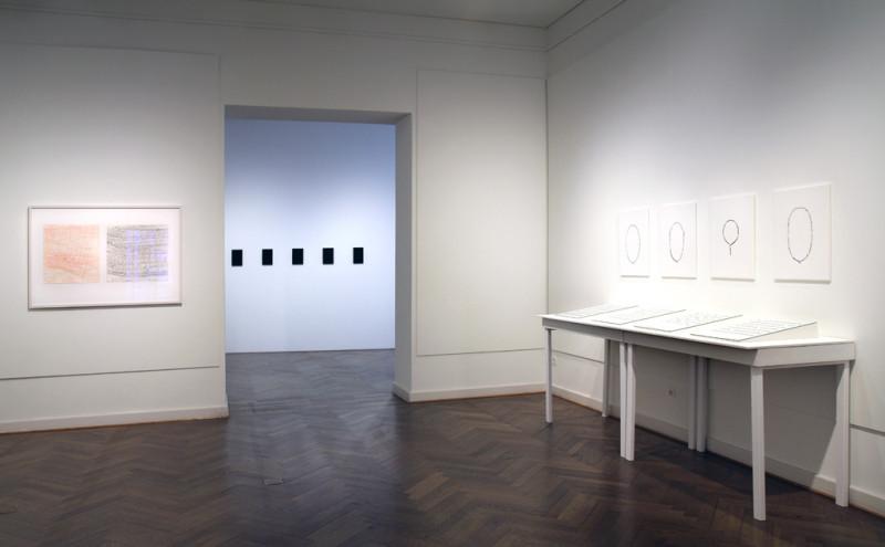 Links sind eine rote und eine blaue Zeichnungen zu sehen. In der Mitte hängen fünf kleine rechteckige schwarze 3D-Drucke an der Wand. Auf der rechten Seite hängen vier Schwarz-Weiß-Fotografien von Gebetsketten.