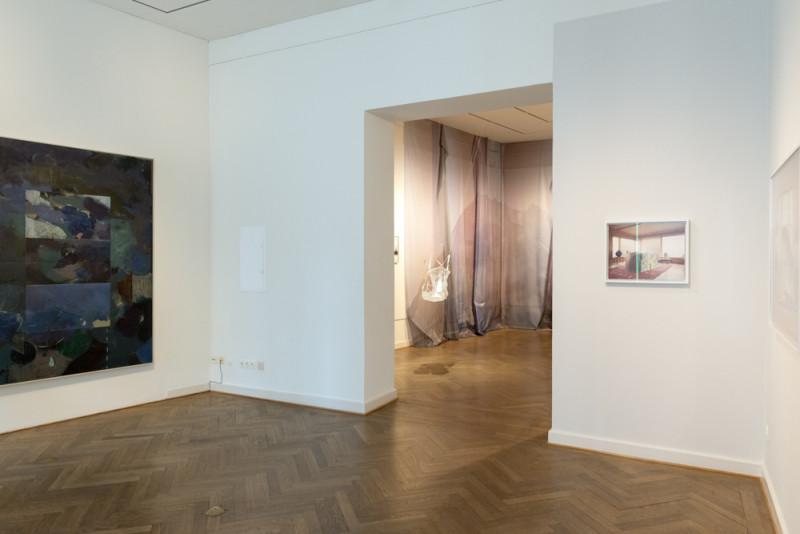 Links hängt ein in dunklen Tönen gehaltenes abstraktes Gemälde. Im mitttleren Raum sind Gurtzeug und Fallschirmseide an der Wand und im Raum angebracht. An der rechten Wand ist eine Fotografie von einem Wohnzimmer zu erkennen.