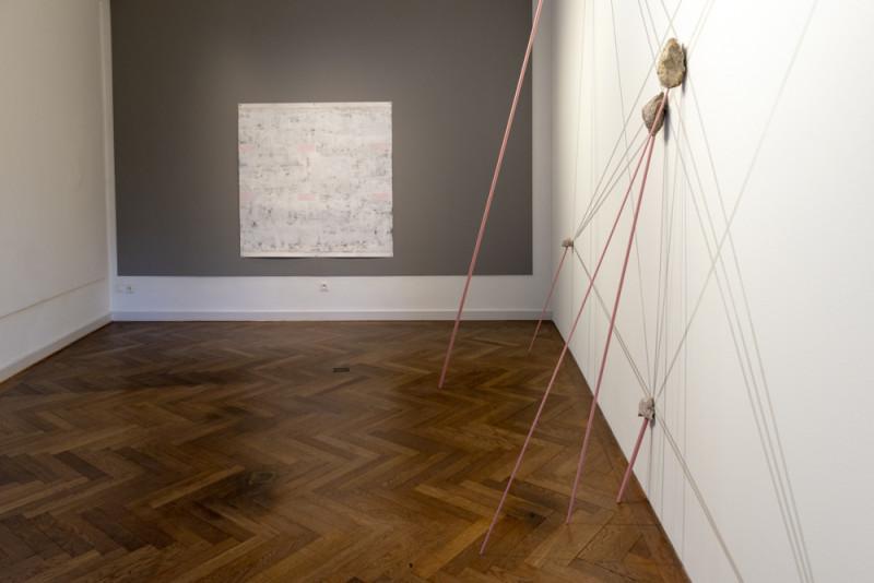 Ein abstraktes in Rosa- und Grautönen gehaltenes Gemälde hängt an einer grauen Wand. Dünne rosafarbene Metallstangen sind an die Wand gelehnt und scheinen Steine darauf zu stützen.