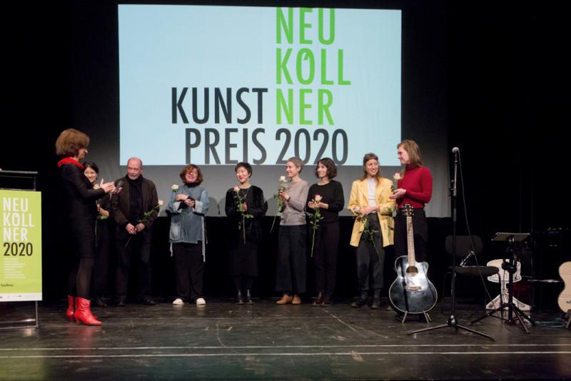 Die acht nominierten Künstler:innen stehen auf der Bühne vor der Projektion des Neuköllner Kunstpreis-Logos mit jeweils einer Rose in der Hand.