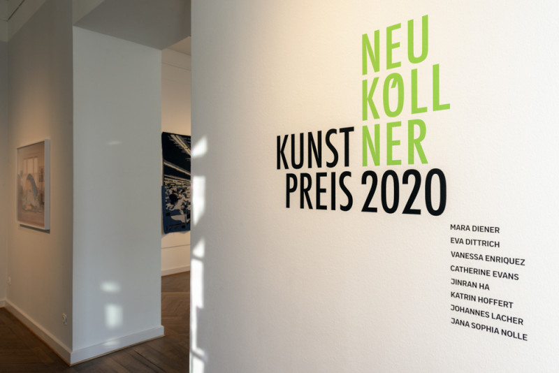 Das Logo zum Neuköllner Kunstpreis 2020 ist in grüner und schwarzer Schrift auf der Wandfläche in der Ausstellung zu sehen.