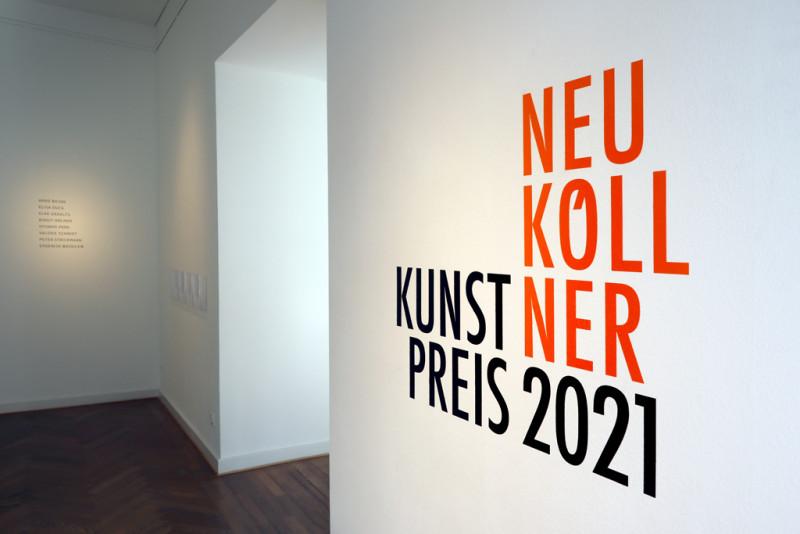 Der Titel der Ausstellung Neuköllner Kunstpreis steht in oranger Schrift auf der rechten Wand im Eingangsbereich der Galerie.