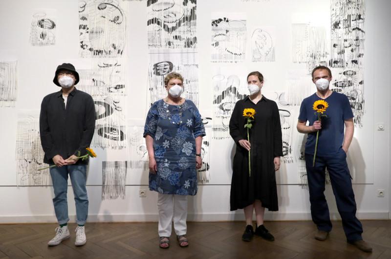 Die Stadträtin Karin Korte steht mit den 3 Preisträgier:innen vor einer schwarz weißen Papierarbeit an der Wand in der Galerie.