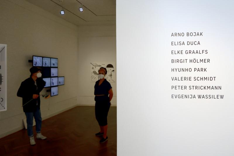 auf der linken Seite stehen auf der Wand die Namen der Nominierten auf der rechten Seite des bildes öffnet sich der Blick in den Ausstellungsraum