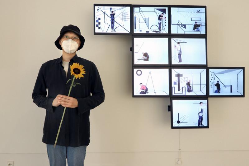 Hyunho Park: vor ihrem Objekt: Time Crystals -  Neun Räume, 2019. Auf der rechten Seite des Bildes hängen 9 Monitore an der Wand.