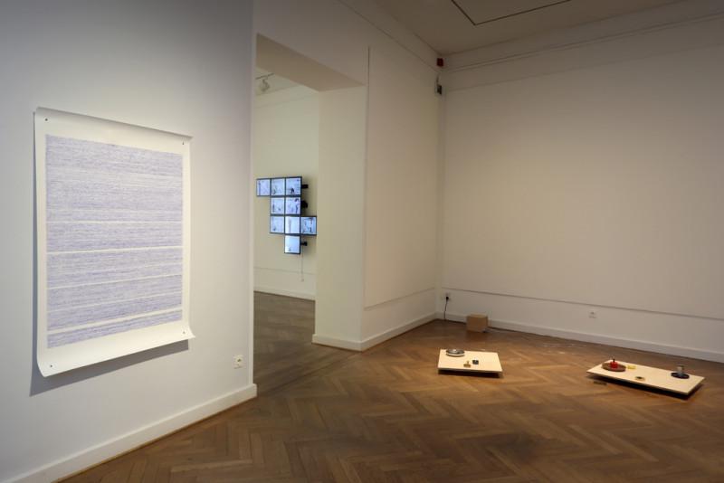 an der rechten Wand hängt eine großformatige Papierarbeit mit blauen Wellenlinien und am Boden auf der rechten Seite steht eine Arbeit, die aus vielen Kleinen schüsseln mit Wasser besteht