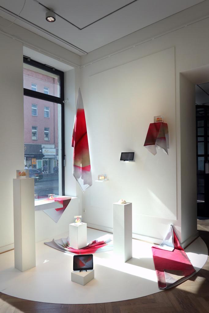 Auf weißem Grund stehen weiße Sockel mit rosa decken und kleine Skulpturen drauf. Die Installation ist vor dem Fenster der Galerie