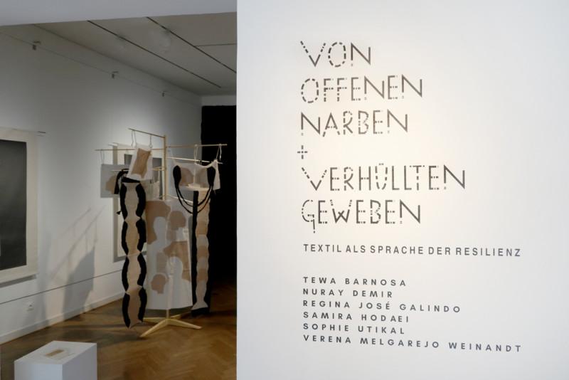 Titel der Ausstellung auf der rechten Seite und Blick in die Ausstellung auf der linken Seite