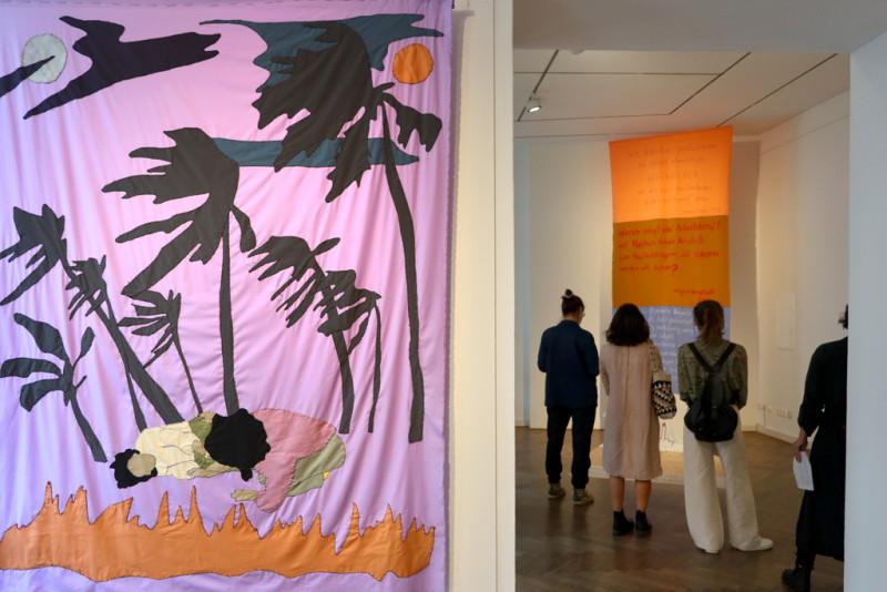 Stoffbild mit Palmen und zwei Frauen im Vordergrund, im Hintergrund Besucher:innen der Ausstellung vor einem Stoffbanner