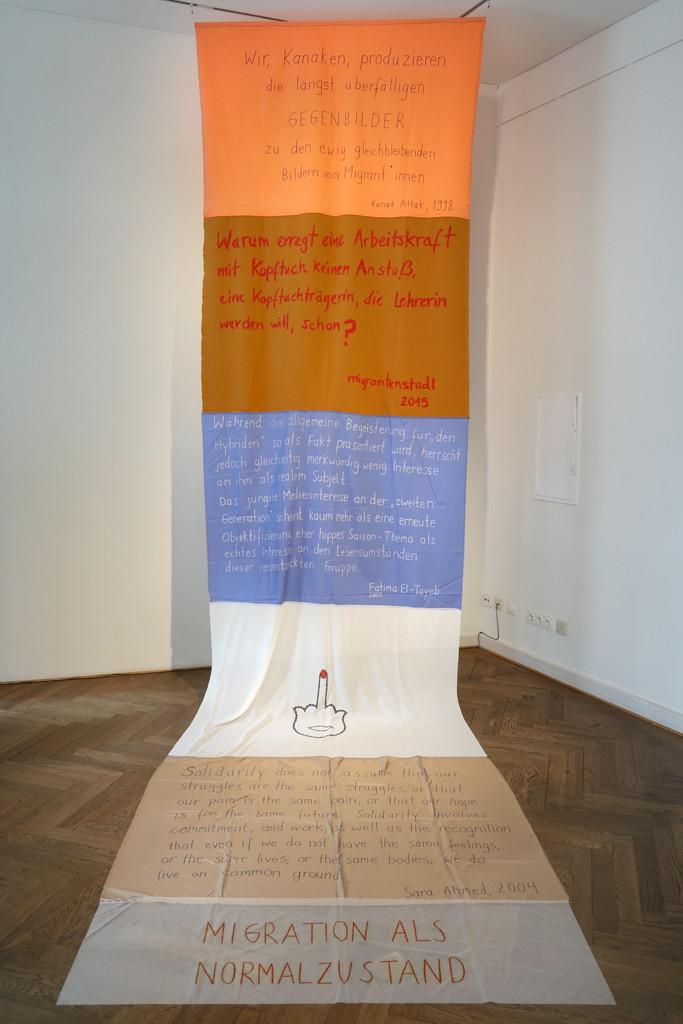 Ein langer Stoffbanner mit Vorderungen hängt von der Decke