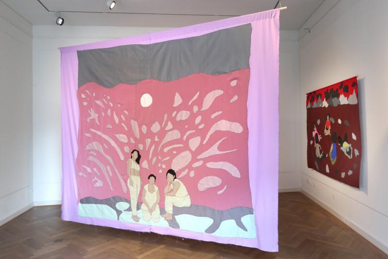großes Stoffbild das in der Mitte des Raums von der Decke hängt und drei Frauen zeigt
