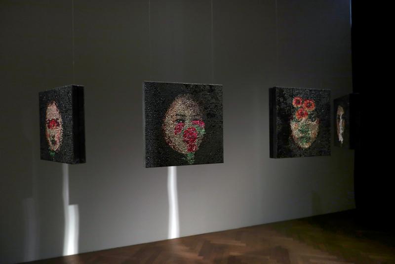 Frauenporträts hängen im Raum