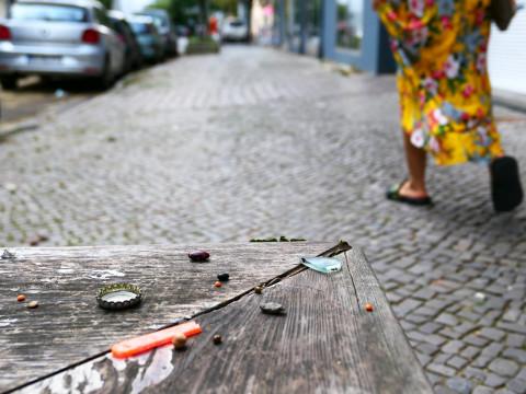 Oben rechts im Bild läuft eine Person, deren Beine nur zu sehen sind, auf dem Fußweg - links unten ist ein Holzbank mit kleinen Gegenständen daruf